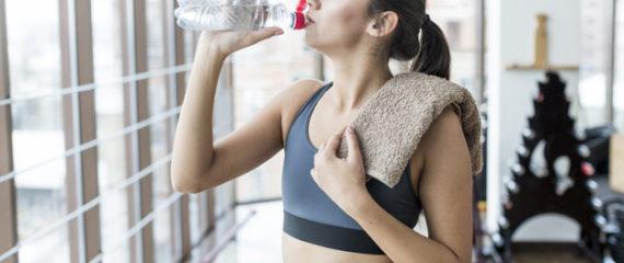 vrouw met handdoek drinken in de sportschool